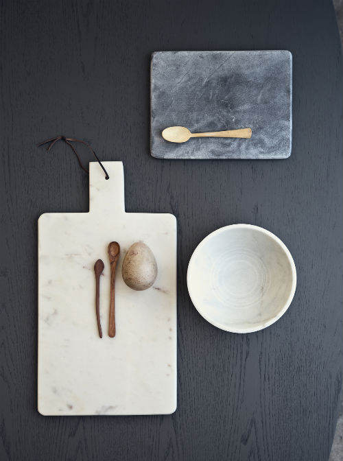 Auf einem schwarzen Tisch liegen Marmorbretter in weiß und grau