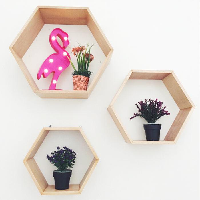 Decoração com luminária led flamingo, plantas e prateleiras hexagonais.