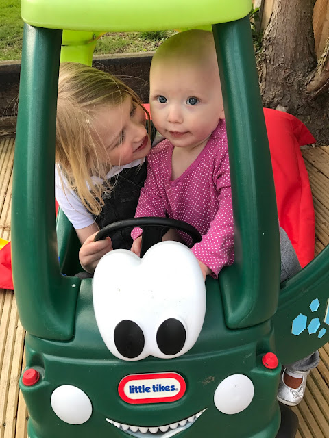 Little trying to climb into the dino Little Tikes car while her big sister is sitting in it it.