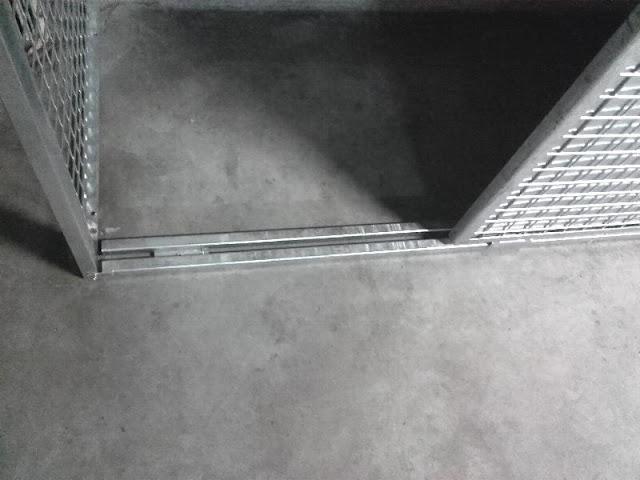 Zabudowa na stanowisku parkingowym w garażu podziemnym. Szafa z drzwiami przesuwnymi, wypełniona siatką i blachą cynkowaną.