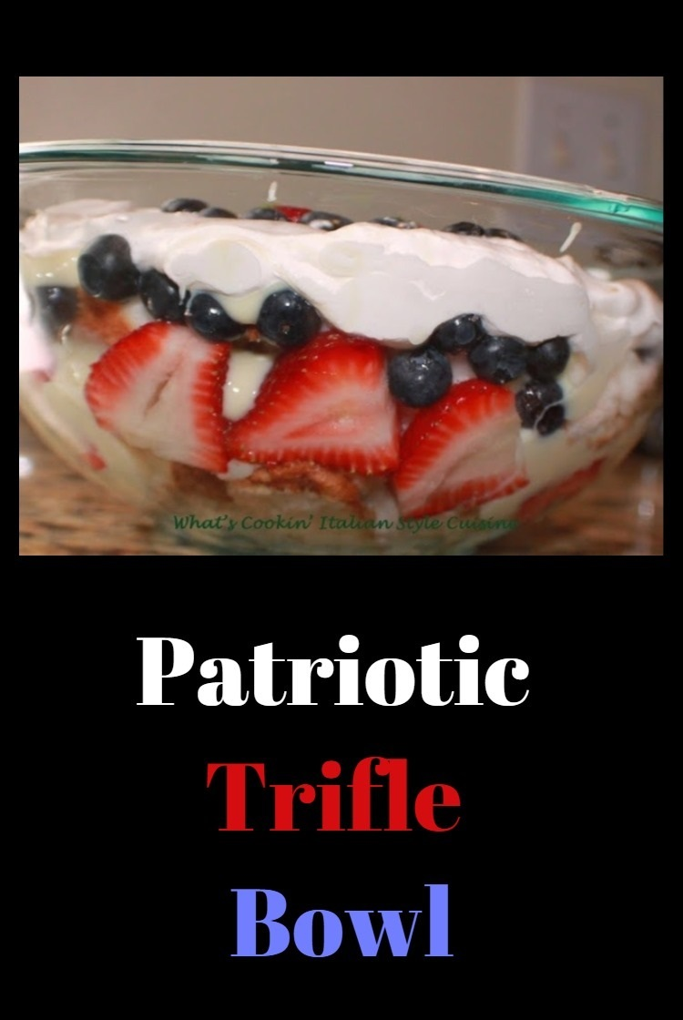This is a festive 4th of July trifle with vanilla pudding,  strawberries, blueberries, pound cake and cream in a clear bowl