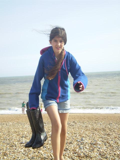 carrying wellies up a shingle beach