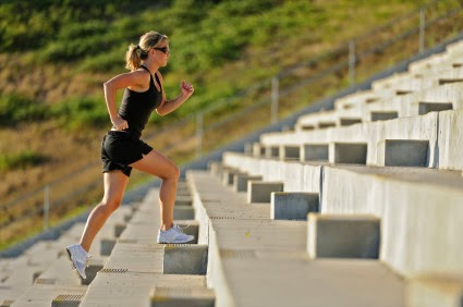 Image of woman running up stadium stairs.