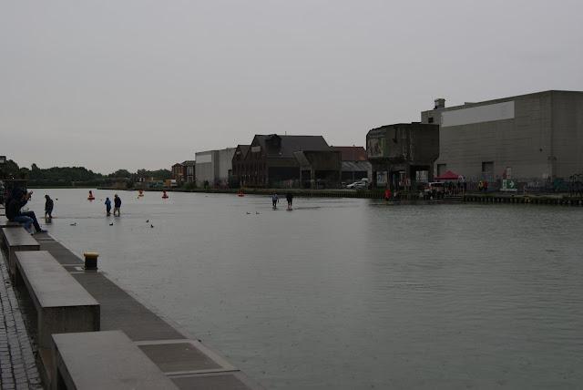 Blick auf das Hafenbecken, in dem Personen auf einem Unterwasser Steg durch das Wasser laufen