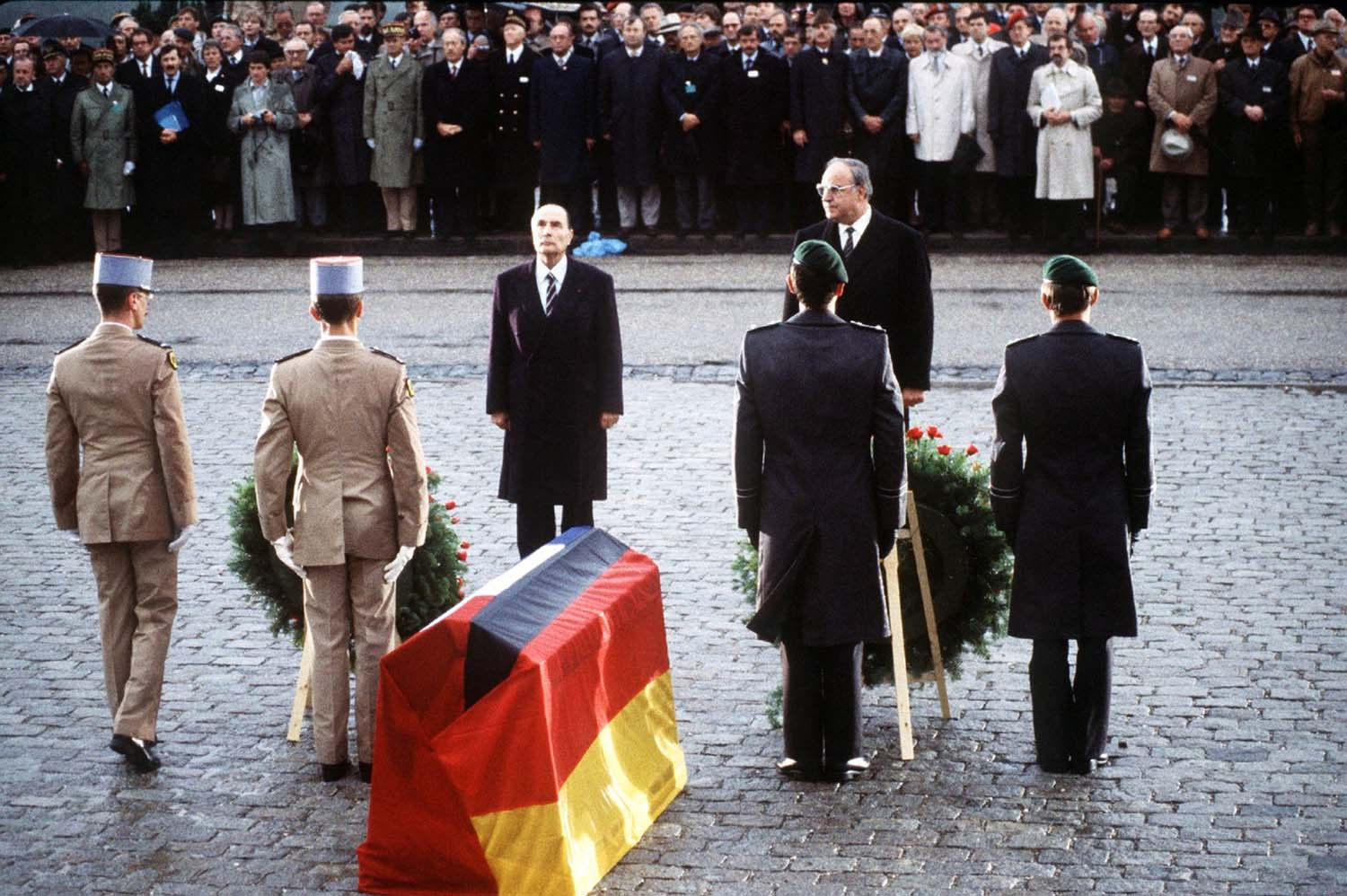 Helmut Kohl and François Mitterrand before the catafalque, covered on one side with a German flag and the other with a French flag.