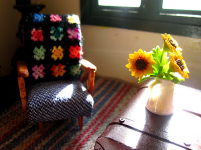 Modern one-twelfth scale miniature vintage armchair with crochet afghan over the back next to an old chest coffee table with a vase of sunflowers on it.