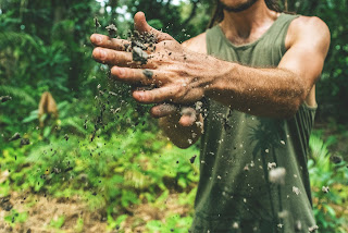 A close-up of a man's hands as he cleans them of dirt. He is wearing a green tank top and standing in the forest. Muddy Man photo by Eddie Kopp.
