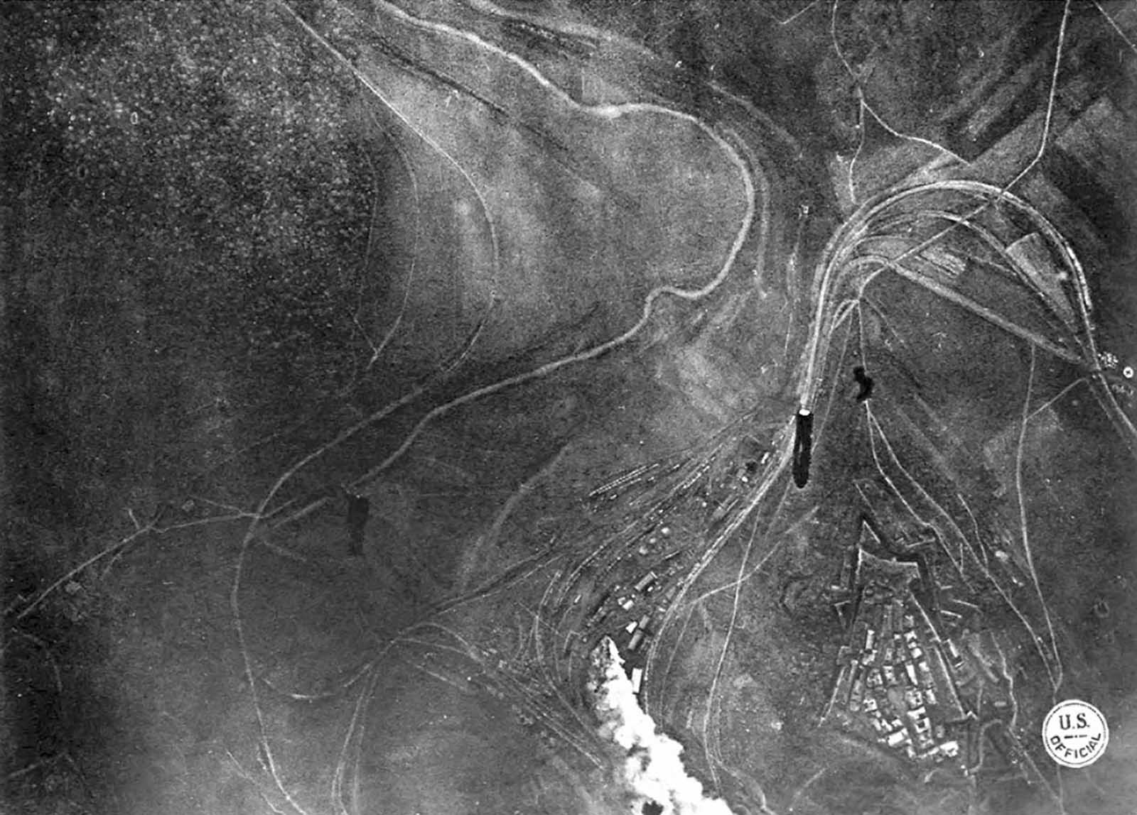 Bombing Montmedy, 42 km north of Verdun, while American troops advance in the Meuse-Argonne sector. Three bombs have been released by a U.S. bomber, one striking a supply station, the other two in mid-air, visible on their way down. Black puffs of smoke indicate anti-aircraft fire. To the right (west), a building with a Red Cross symbol can be seen.