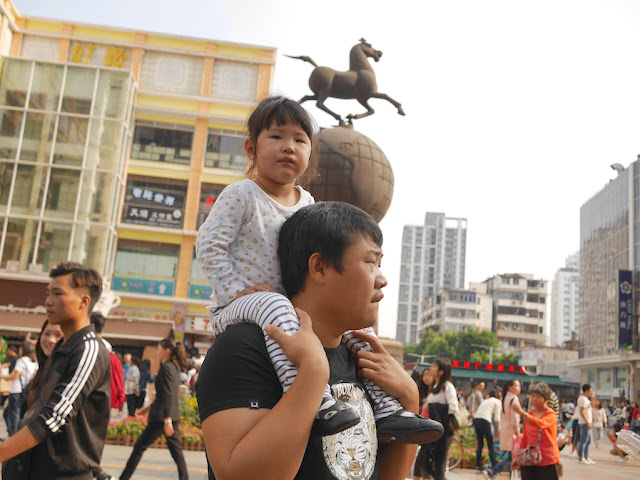 little girl riding on a man's shoulder's
