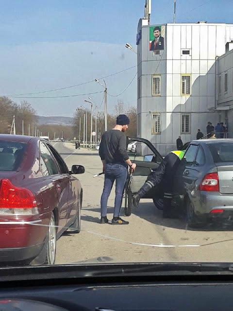 Гаишник в Грозном (Чеченская Республика) проверяет машину, попросив водителя машины поддержать жезл и автомат.