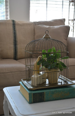 brass bird cage, marble parrot bookend, greenery, vintage grain sack in green