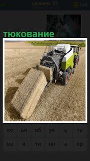тюкование сена, идет машина по полю и собирает сено