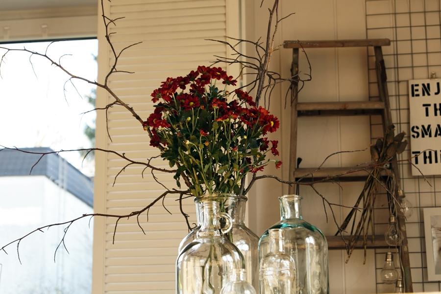 Blog + Fotografie by it's me! - dunkelrote Chrysanthemen mit Zweigen, Glasflaschen, alte Leiter mit Glühbirnen