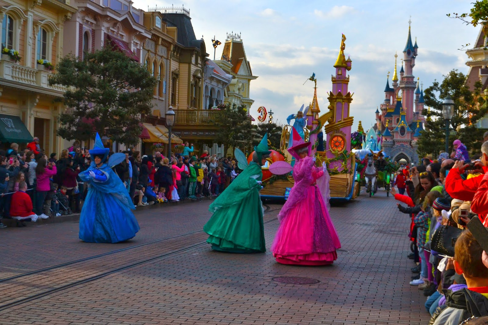 the disneyland parade. Flora Fauna and Merryweather can be seen walking in front of th sleeping beauty float