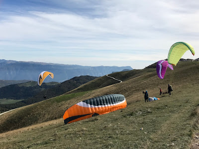 Paraglidere som legger ut fra skråningen.