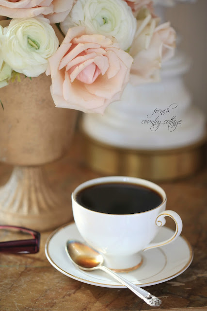 A cup of coffee on the nightstand with flowers