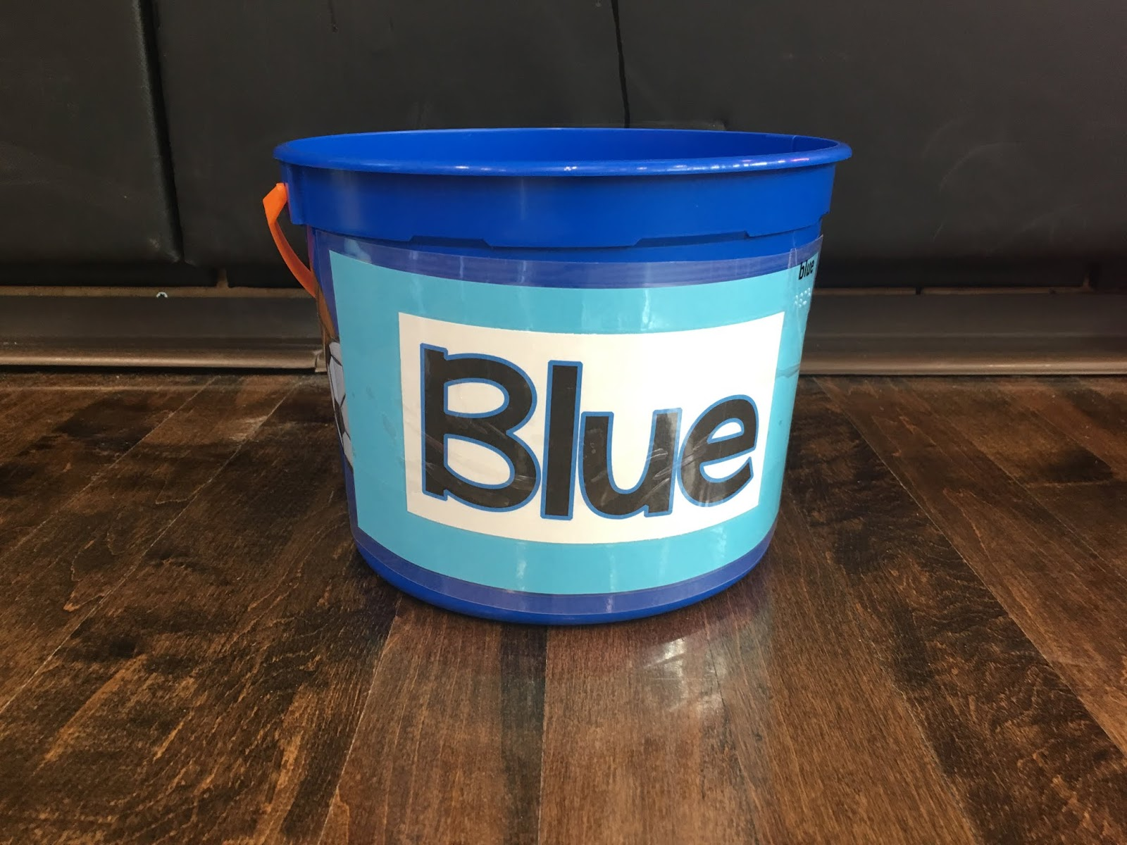 """a blue bucket with large print word """"blue"""" and Braille label"""