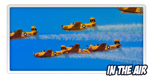 six yellow airplanes in formation flying in the air show