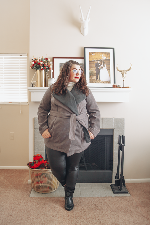 An outfit consisting of a grey wrap coat over a white and black turtleneck top, black coated pants, and black chelsea boots.
