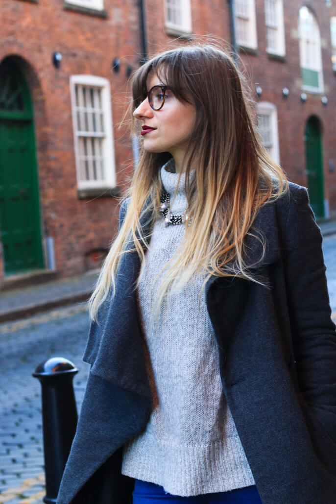 Winter fashion girl in long grey coat and turtle neck jumper