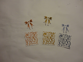 3 die cut  filigree presents, white with re, brown and blue behind, with matching bows