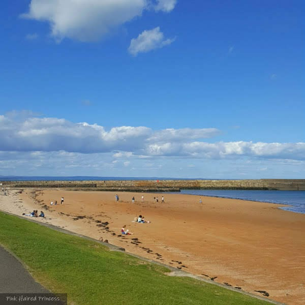 sandy beach, grass and pier in background with people sitting on Scottish beach in the sun