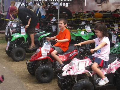 Two boys on red or green mini atvs, girl on a pink one