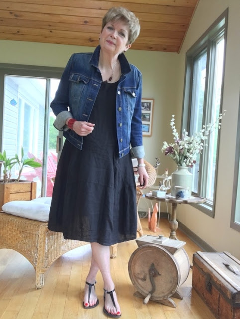 woman in black dress, black sandals, and denim jacket