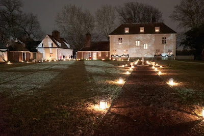 Grounds of Pennsbury Manor lit by lanterns and luminaries.