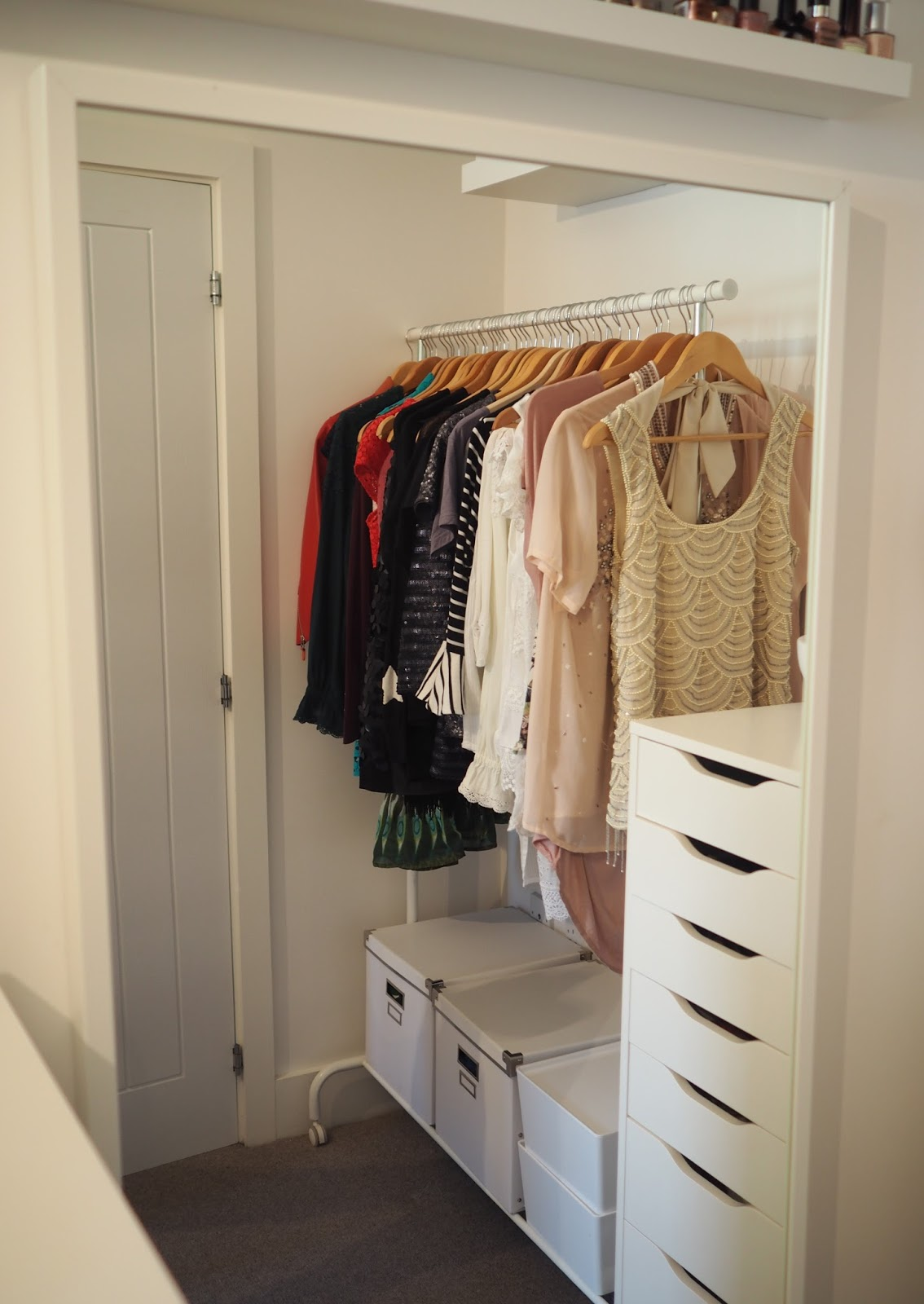 Walk in closet using white Ikea furniture, full-length white mirror