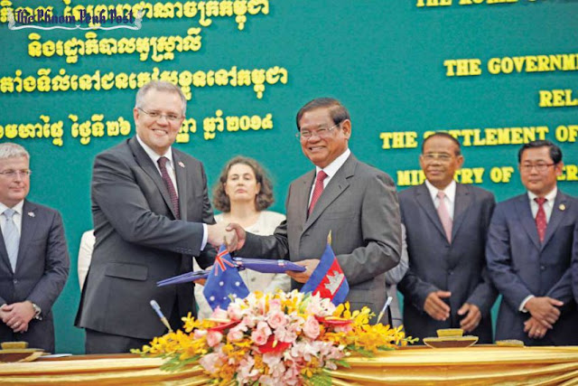 Scott Morrison (left), the then-Australian immigration minister, shakes hands with Interior Minister Sar Kheng after signing the refugee deal in September, 2014. Heng Chivoan