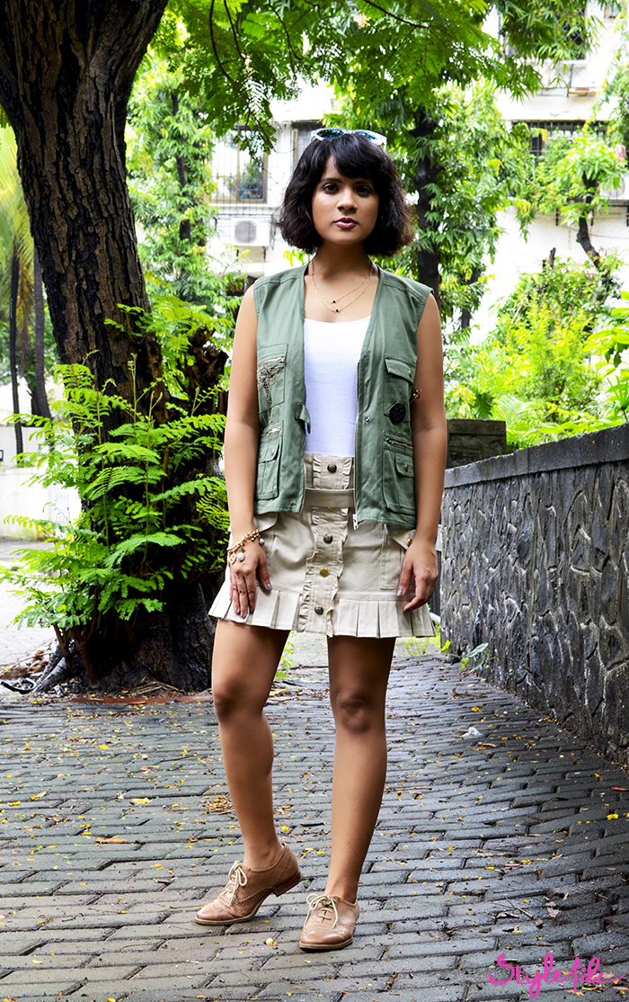 An image of a women fashion blogger wearing an olive green jacket vest with a beige pleated skirt and oxford shoes, reflective sunglasses, gold accessories and bronze eye makeup