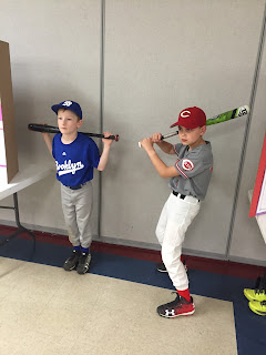 Two boys dressed as baseball players standing like wax art