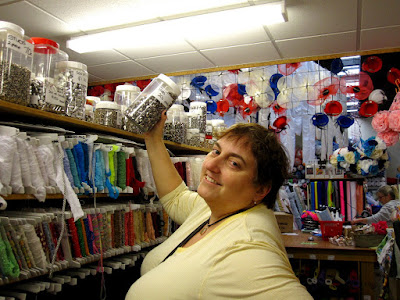 Woman in a haberdashery section of a craft shop, holding up a large jar of studs.