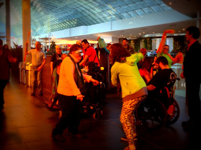 People dressed colourfully for spontaneous dancing in an inside downtown mall