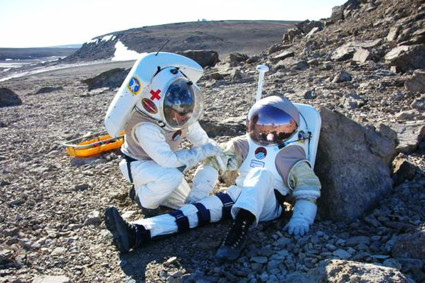 to people in flight suits training on a rocky terrain on earth