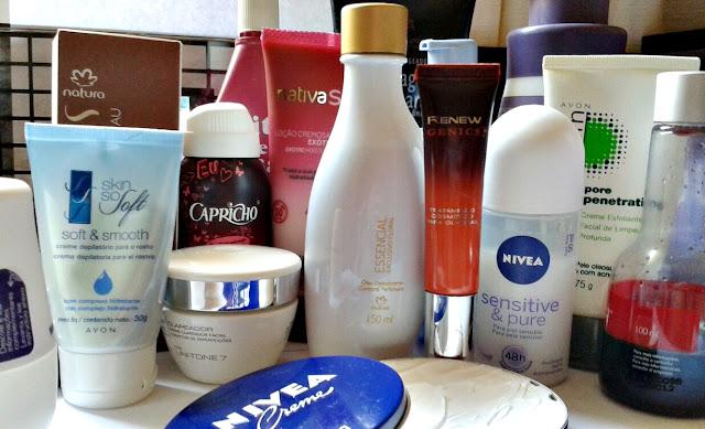 Vários recipientes de cosméticos distribuídos em toda a foto. Desde hidratantes a desodorantes e óleos. À frente um pote redondo aberto, deixando aparecer o conteúdo de dentro.
