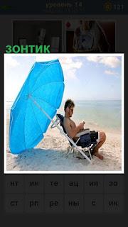 сидит мужчина на берегу под зонтиком от солнца