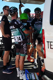Jay McCarthy is holding a young boy in his arms. The boy is wearing a bright lime green cycling helmet. They are facing the group of Bora Hansgrohe riders who are standing in a circle around him. A Bora technician is standing in black on the left hand side. They are all under the shade of the open tailgate of their team bus.