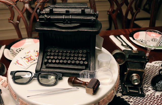 Vintage camera, typewriter, stamp pad, glasses, tweezers, magnifying glass as centerpiece for spy party