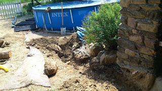 Starting to dig the trench, a very big stone is right in our way and the existing drainage pipe is visible