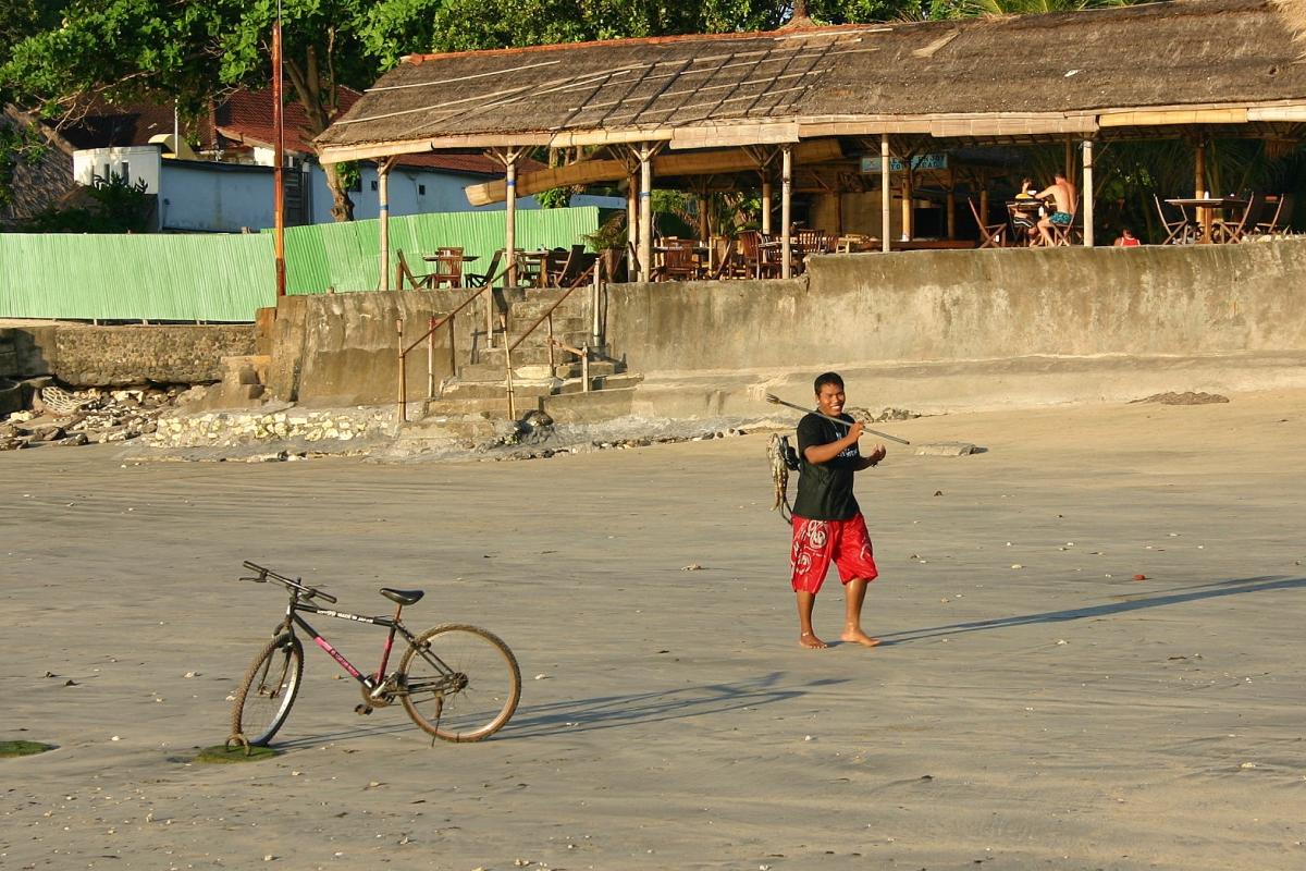 생선을 잡고 돌아가는 발리 현지인과 해변의 자전거