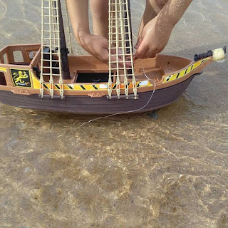child's feet and toy pirate ship in shallow water