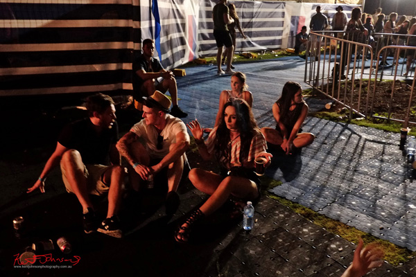 Getting late, friends resting on the plastic matting. Harbour Life Music Festival Sydney 2016. Photographed by Kent Johnson for Street Fashion Sydney.