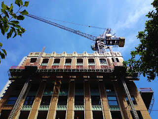 Tower crane rises to blue sky on top of older office building