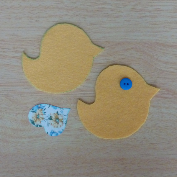 Two bird pattern pieces fabric wing and blue button