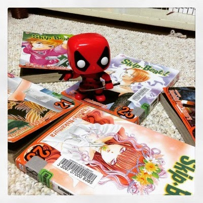 A small bobblehead dressed in a red and black bodysuit stands in the centre of five volumes of Skip Beat. The mangas are arrayed in a fan pattern. The visible covers feature a young Japanese girl with long, deep red hair and an older Japanese girl with short, more carroty red hair. The others are indistinct.