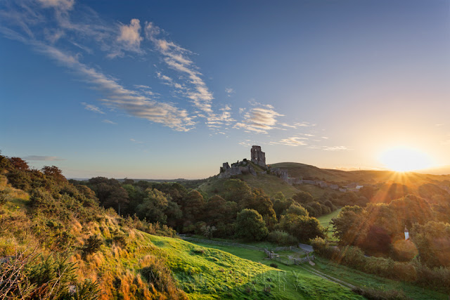 The ruins of Corfe Castle with the rising sun behind them from West Hill
