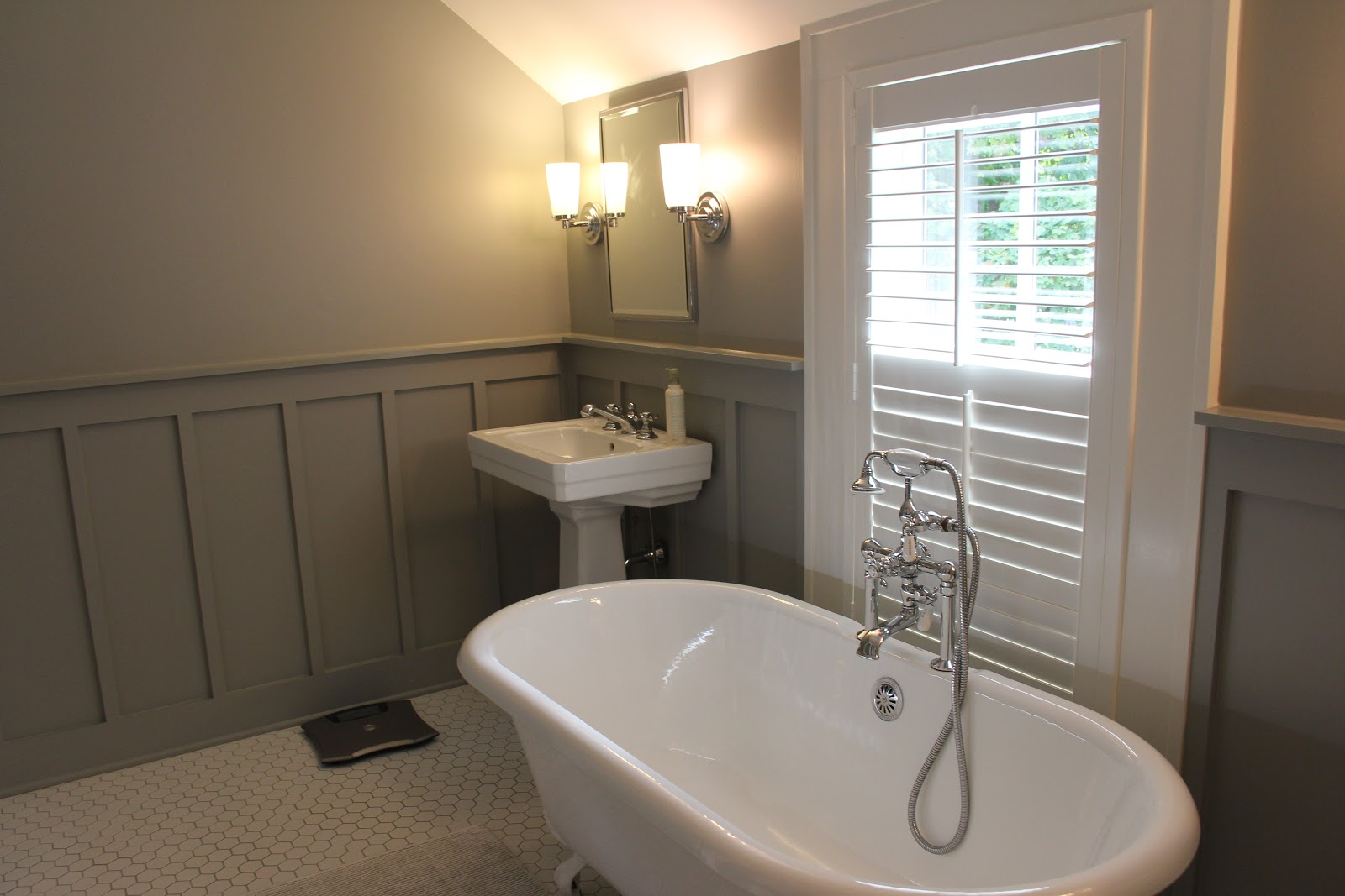 White and grey modern farmhouse bathroom with clawfoot tub and plantation shutters on Hello Lovely Studio