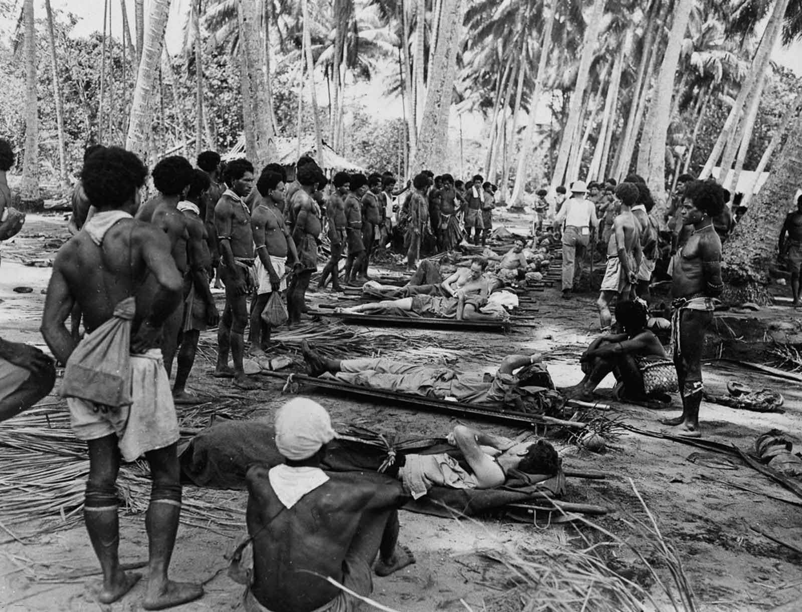 Stretcher bearers pause for a rest in a coconut grove en route to aid stations in the rear.
